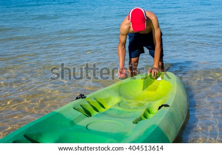 Man cleans kayak with water at sea - stock photo