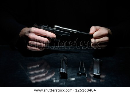 man cleans the disassembled gun on dark background - stock photo