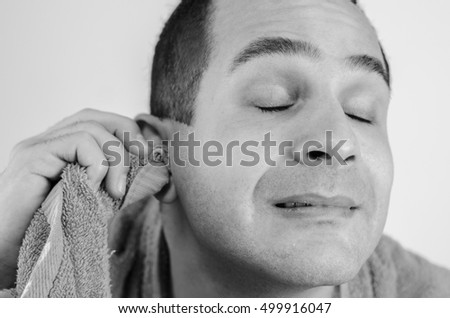 man cleans the ears with a towel