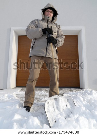 Man clearing driveway of snow with shovel after heavy snowing - stock photo