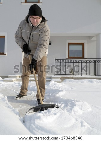 Man clearing path to his house of snow with shovel after heavy snowing - stock photo