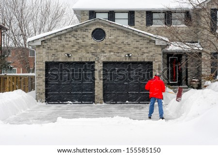 Man clearing snow on his driveway - stock photo