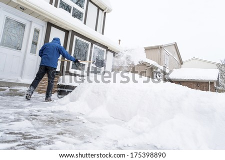 Man Clearing Snow with a Shovel - stock photo