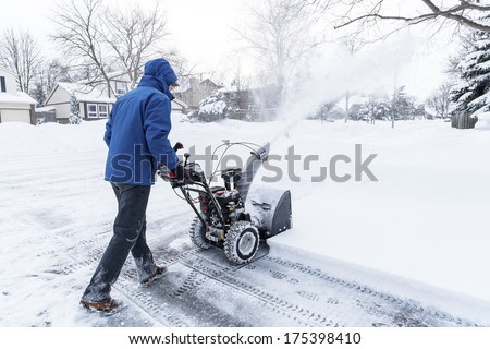 Man Clearing Snow with a Snow Blower - stock photo