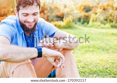 Man clicking on a screen of his smart watch sitting on a grass in a park