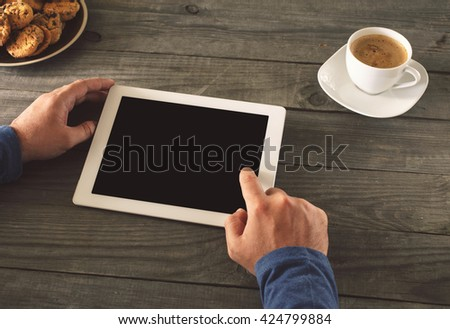 man clicks on the screen tablet with blank screen for your text sitting behind a rustic wooden table at home
