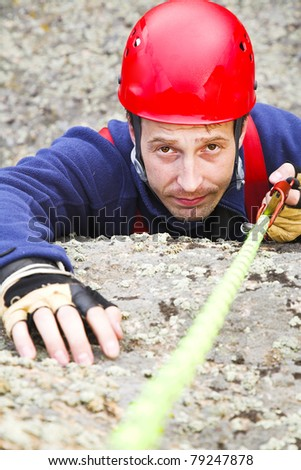 man climber in red helmet with rope