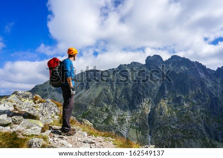 Man climber with helmet admiring the view from the edge of a cliff in the mountains. High Tatra, Slovakia