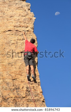 Man climbing a rock face with the moon - stock photo