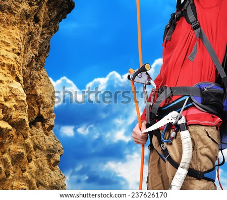 man climbing a rope on a rock - stock photo