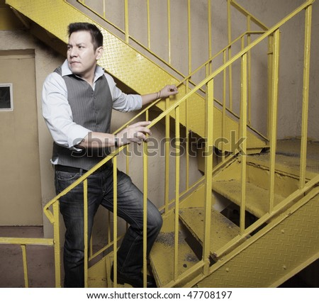 Man climbing a yellow staircase and looking over his shoulder