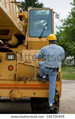 man climbing aboard machinery in preparation of the workday - stock photo