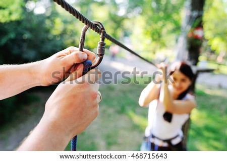 man climbing carbine mount on background asian girl in the ropes course