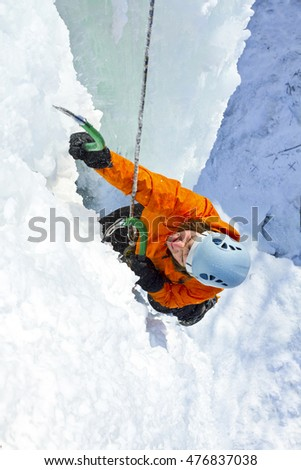 Man climbing frozen waterfall.