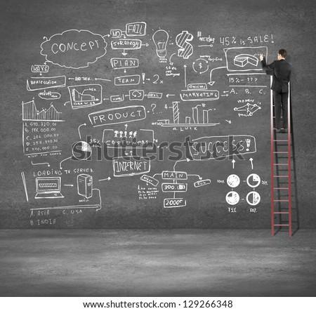 man climbing on ladder drawing business plan - stock photo