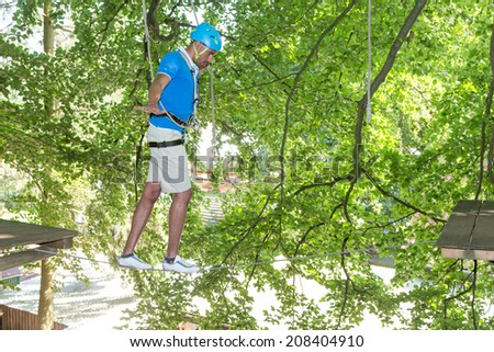 Man climbing on tightrope in high rope course - stock photo