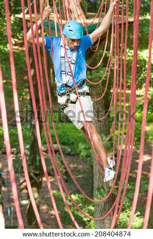 Man climbing over obstacles at high rope court - stock photo