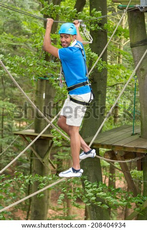 Man climbing over obstacles at high rope court