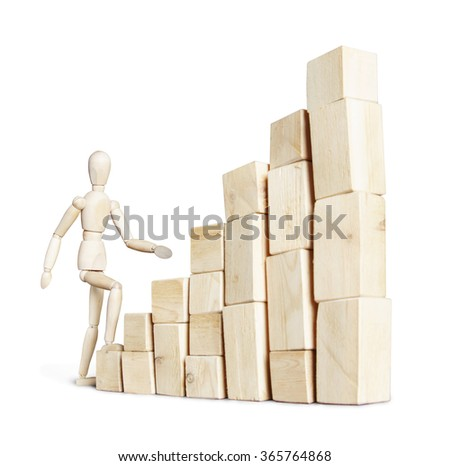Man climbing to high stack of blocks. Abstract image with a wooden puppet - stock photo