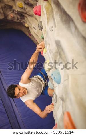 Man climbing up rock wall at the gym - stock photo