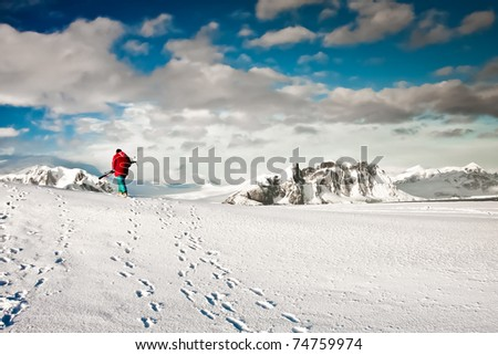 Man climbs on a snow slope with skis in hand. Antarctica.
