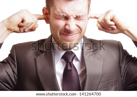 man clogging his ears because of noise - stock photo