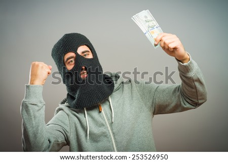 man close up thief in a mask  holding the money  - stock photo