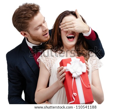 Man closes eyes of his girlfriend, isolated on white - stock photo
