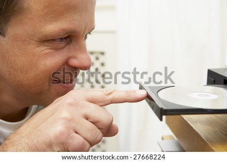 Man Closing DVD Player With Finger