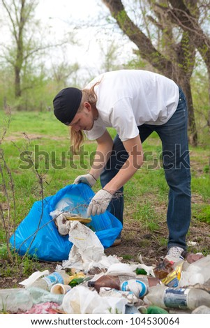 man collecting rubbish in the forest - stock photo