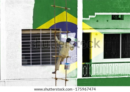 Man coloring or painting Brazilian flag manually on wall hanging on a rope ladder - stock photo