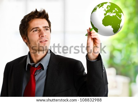 Man colouring the world of green - stock photo