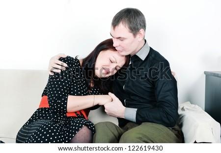 Man comforting his woman on the sofa - stock photo