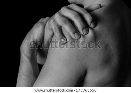 Man compresses his shoulder, pain in the shoulder, black and white image - stock photo