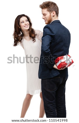Man conceals the present behind the back from his pretty girlfriend, isolated on white - stock photo
