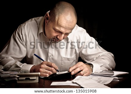 Man concentrating while paying bills for household finances - stock photo