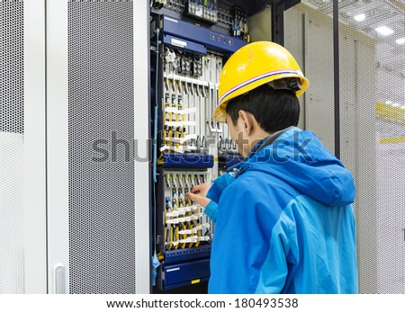 Man connecting network cables to switches - stock photo