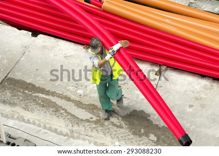 man construction worker working  to repair  the water, fiber optic and sewer pipes in the  city at street - stock photo