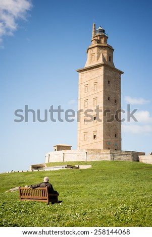 Man contemplating Hercules tower lighthouse in La Coruna, Spain in a sunny day - stock photo