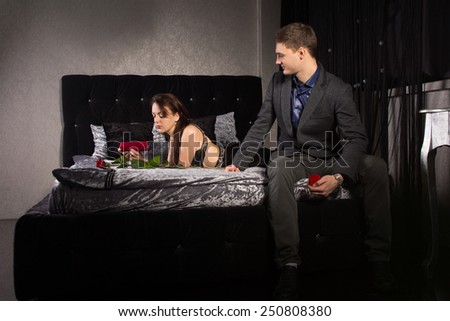 Man contemplating proposing to his girlfriend sitting on the end of the bed with the ring box in his hand plucking up his courage - stock photo