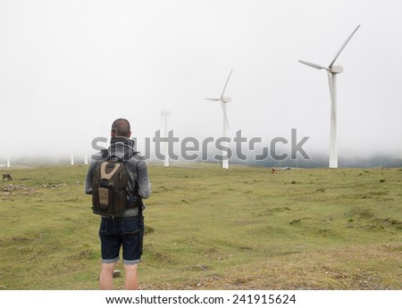 Man contemplating wind turbines in nature on a foggy day