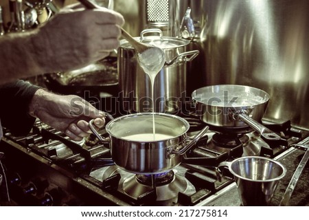 man cooking and making white sauce  - stock photo