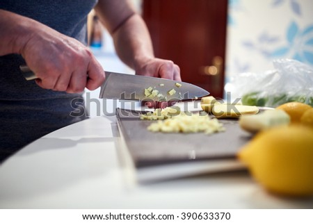 Man cooking at home, chopping ginger for a recipe