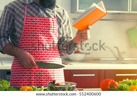 man cooking at kitchen making healthy vegetable salad and reading recipe book