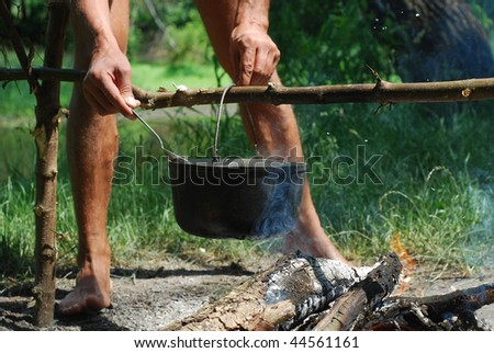 man cooking meal in tourist pot - stock photo