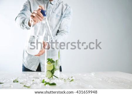 Man cooks homemade lemonade, pours sparkling water from soda syphon to vintage bottle with ice limes mint and cucumber slices to make refresment beverage for summer time in cafe - stock photo