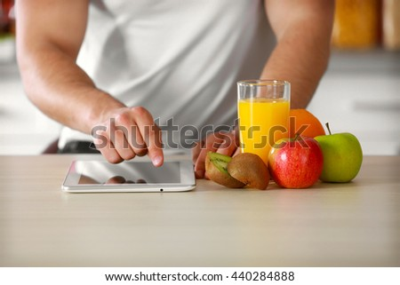 Man counting calories on tablet - stock photo