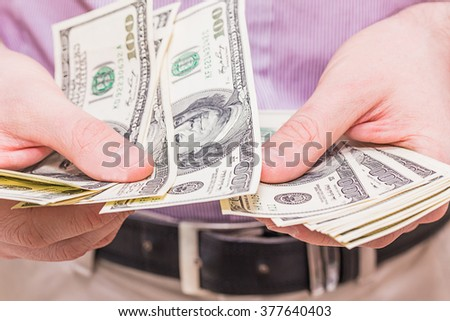 Man counting money. Dollars in man's hands. A man in business clothes with dollars.