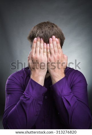 Man covered his face with hands - stock photo