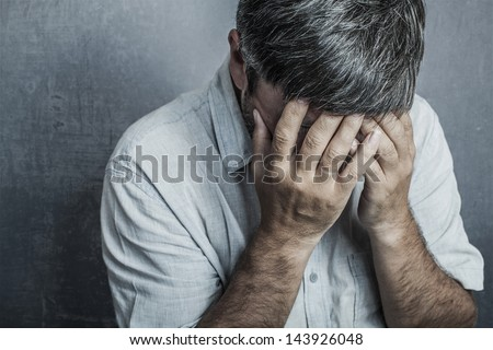 man covered his face with his hands - stock photo